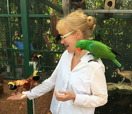 White woman with green bird on shoulder.